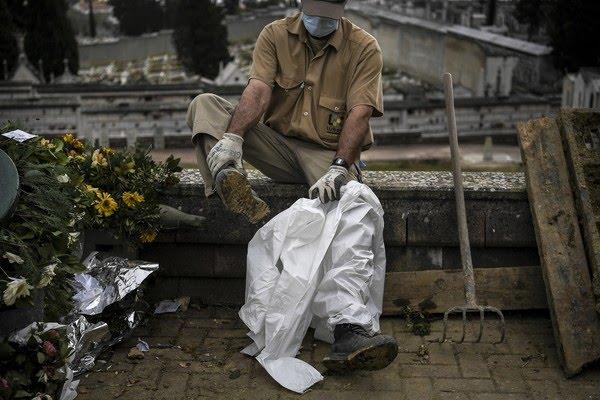 Coveiro coloca roupa de proteção contra a Covid-19 em cemitério de Lisboa, Portugal, nesta quinta-feira (19) — Foto: Patrícia de Melo Moreira/AFP
