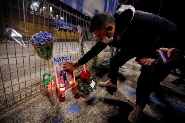 Homem faz homenagem ao astro do futebol argentino Diego Maradona, morto nesta quarta-feira (25), do lado de fora do estádio San Paolo em Nápolis, na Itália — Foto: Ciro De Luca/Reuters