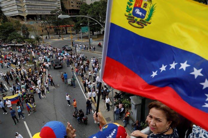 Apoiador de Juan Guaidó segura bandeira da Venezuela durante protesto contra do governo de Nicolás Maduro nesta quarta-feira (30) em Caracas — Foto: Manaure Quintero/Reuters