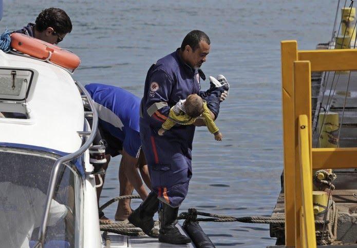Socorrista do Samu leva um bebê no colo após uma embarcação naufragar em Mar Grande, na Baía de Todos-os-Santos, na Bahia