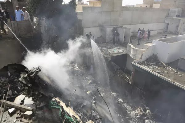 Bombeiros tentam controlar fogo causado pela queda de um avião comercial na área residencial de Karachi, no Paquistão — Foto: Fareed Khan/AP