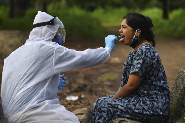 Uma equipe médica usando Equipamento de Proteção Individual (EPI) coleta uma amostra de esfregaço nasal de uma mulher durante um exame da Covid-19 em Nashik, no estado de Maharashtra, na Índia, em 13 de setembro de 2020. — Foto: INDRANIL MUKHERJEE / AFP