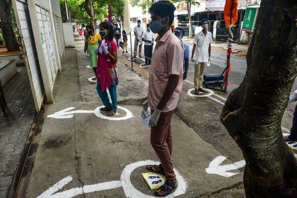 Jovens ficam em fila com marcas de distanciamento social no chão antes de entrar em um centro de exames de admissão para ingresso nas principais faculdades de medicina do país, em Chennai, no estado de Tamil Nadu, na Índia, em 13 de setembro de 2020. — Foto: Arun SANKAR / AFP