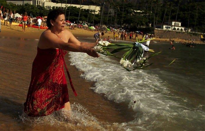 RJ: Mulher lança flores ao mar na Praia Vermelha, em uma tradição anual dos seguidores da religião umbanda — Foto: Pilar Olivares/Reuters
