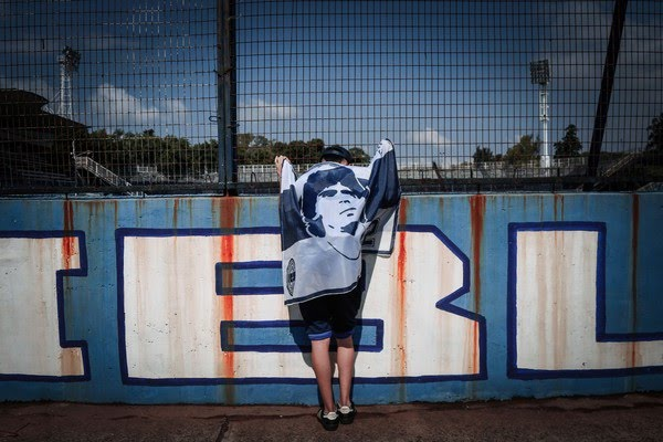 Torcedor enrolado em bandeira vai ao estádio do Gimnasia, onde Maradona dona trabalhava como treinador — Foto: Maria Paula Avila/AP Photo