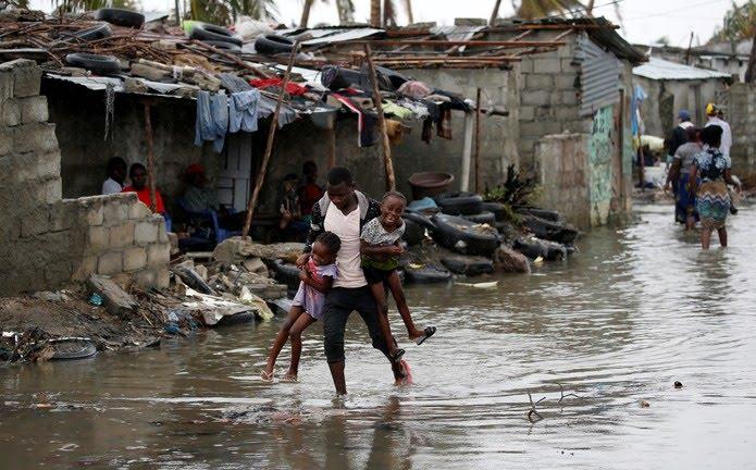 Homem carrega crianças em área inundada na cidade de Beira, Moçambique, neste domingo (24). — Foto: Reuters/Siphiwe Sibeko
