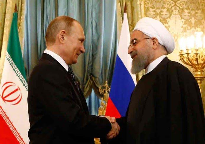 O presidente russo Vladimir Putin (esq.) aperta a mão do presidente iraniano Hassan Rohani durante encontro no Kremlin